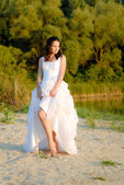Young beautiful bride standing by river thoughtful — Stock Photo