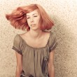 Stock Photo: Young beautiful redhaired teenage girl playing with hair
