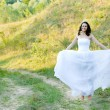 Foto Stock: Young beautiful bride on green lawn passage