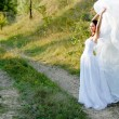 Young beautiful bride on green lawn passage — Stock Photo #18247611
