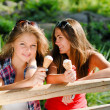 Two happy girl friends eating ice cream outdoors — Stock Photo #18247649