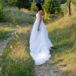 Young beautiful bride on green lawn passage — Stock Photo