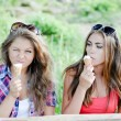 Two happy girl friends eating ice cream outdoors — Stock Photo