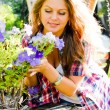 Young happy woman taking care of petunia flowers — Stock Photo