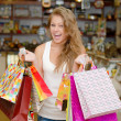 Stock Photo: Happy young womwith shopping bags