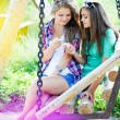 Two young girl friends looking on mobile phone — Stock Photo