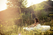 Young beautiful bride lying in green grass — Stock Photo