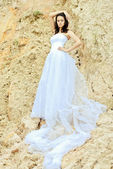 Young beautiful bride among sands thoughtful — Stock Photo