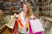 Glad ung kvinna med kassar och påsar — Stockfoto