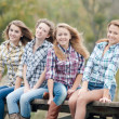 Four girls sitting on river bridge — Stock Photo #18524683