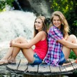 Two teen girls sitting by waterfall — Stock Photo #18524945