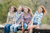Four girls sitting on river bridge — Stock Photo