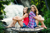 Two teen girls sitting by waterfall — Stock Photo