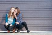 Teenage girls sharing secret — Stock Photo