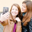 Two teen girls taking picture of themselves using tablet pc — Stock Photo #18937131