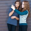 Two teen girls taking picture of themselves using tablet pc - Stock Photo