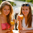 Two happy women drinking orange juice — Stock Photo