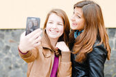 Two teen girls taking picture of themselves using tablet pc — Стоковое фото