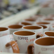Many white coffee mugs in a line for sale — Stock Photo