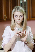 Smiling young woman sending a text message at home — Stock Photo