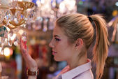Beautiful blond woman in lamp shop — Stock Photo