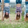Four young girls hanging upside down in park — Stock Photo #21261985