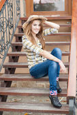 Pretty smiling teenage girl sitting on the stairs — Stock Photo