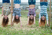 Four young girls hanging upside down in park — Stock Photo