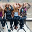 Four school girls sitting on river bridge — Stock Photo
