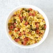 Bowl of uncooked macaroni shells - Stock Photo