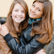 Brunette and blond haired girls friends laughing — Stock Photo