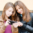 Stock Photo: Two girls friends with mobile touch phone