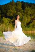 Bride standing at the riverside under tree sunset — Stock Photo