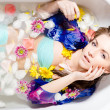 Beautiful lady taking a bath with flower petals — Stock Photo