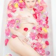 Stock Photo: Beautiful lady taking bath with flower petals