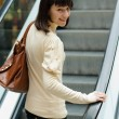 A beautiful young woman on escalator at shopping center — Stock Photo