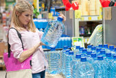 Beautiful young blond woman in shop selecting clean water — Stock Photo