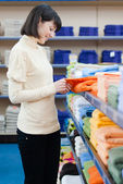 Pretty young woman shopping towels — Stockfoto