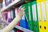 Girl's hand taking big folder from the shelves with office files. — Stock Photo