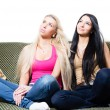 Portrait of two pretty young girlfriends or sisters sitting together — Stock Photo #23645151