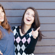 Two pretty happy Teen Girl Friends Laughing & pointing to copyspace — Stock Photo