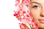 Closeup on beautiful girl face & pink flowers, perfect skin & lips. — Stock Photo