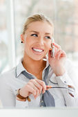 Beautiful business woman talking on cell phone while looking at copyspace — Stock Photo