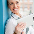 Smiling young business woman using tablet PC while standing relaxed near window at her office — Stock Photo