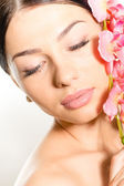 Beautiful girl face with eyes closed & pink flowers, perfect skin and lips on white — Stock Photo