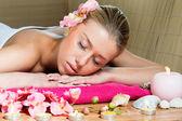 Piękna kobieta relaks podczas masażu z kwiatami, doskonałej skóry — Zdjęcie stockowe