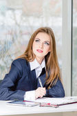 Businesswoman in man's suit signing with pen at her office fashion styled — Stock Photo