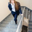 Young business woman wearing man's suit walking on stairs — Stock Photo #25261243