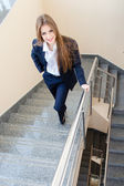 Young business woman wearing man's suit walking on stairs — Foto de Stock