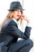 Young business woman wearing man's suit, hat in office — Stock Photo